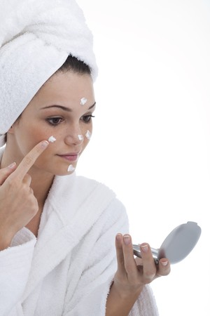 Close-up of a young woman applying moisturizer photo