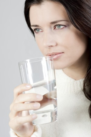 Portrait of a young woman drinking a glass of water. Stock Photo - 8021956