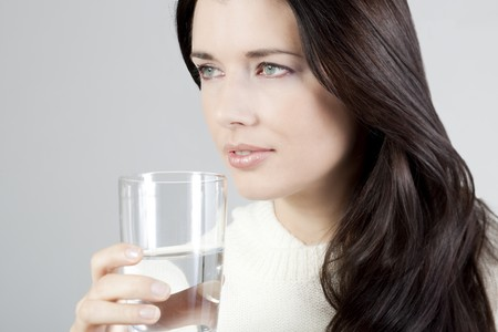Portrait of a young woman drinking a glass of water. photo