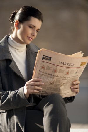 Young businesswoman reading newspaper outdoors photo