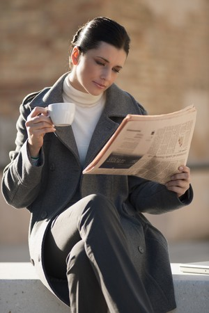 Young businesswoman taking a rest with newspaper and coffee Stock Photo - 8021931