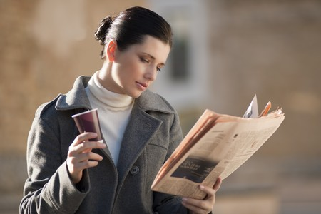 Young businesswoman taking a rest with newspaper and coffee photo
