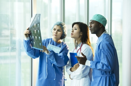 Multi-ethnic doctors discussing about a patient x-ray exam Stock Photo - 8180362