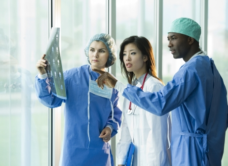 Multi-ethnic doctors discussing about a patient x-ray exam Stock Photo - 8180369