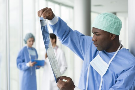 Male surgeon reading x-ray photo