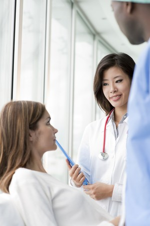 Doctor and surgeon speaking with a female patient photo