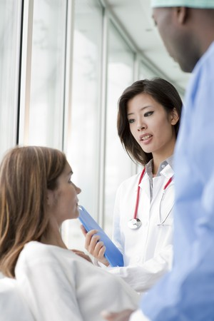 Doctor and surgeon speaking with a female patient Stock Photo - 8185149