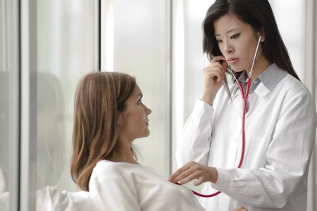 Female doctor checking patient's heart with stethoscope Stock Photo - 8185153