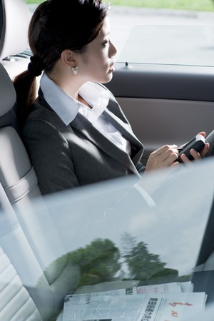 passenger vehicle: Young chinese business woman inside a car Stock Photo
