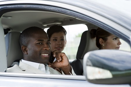 Multi-ethnic businesspeople sharing a car photo