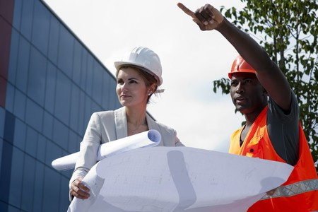 Young female engineer discussing a building project with a construction worker photo
