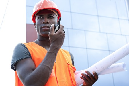 construction safety: Construction worker speaking on Walkie-Talkie