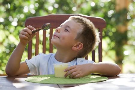 Schattige kleine jongen oudding buiten eten