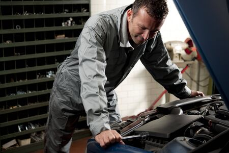 Smiling mechanic controlling car engine photo