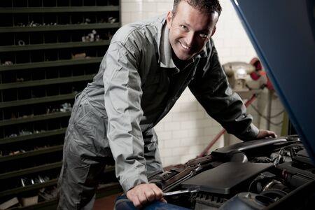 auto mechanic: Smiling mechanic controlling car engine Stock Photo