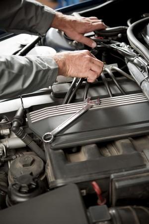 Male hand repairing car engine photo