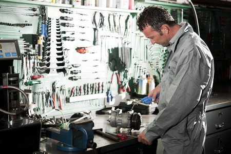 Close-up of a smiling mechanic inside his auto repair shop Stock Photo - 8190137