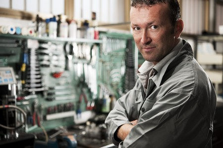 Close-up of a smiling mechanic inside his auto repair shop photo