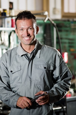 Close-up of a smiling mechanic inside his auto repair shop Stock Photo - 8184345