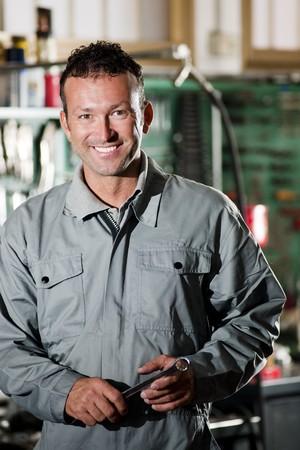 mecanico: Primer plano de un mec�nico sonriente dentro de su tienda de reparaci�n autom�tica  Foto de archivo