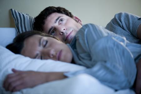 sleeplessness: Immagine di un paio in letto, uomo non pu� dormire