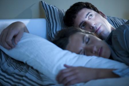 insomnio: Imagen de una pareja en cama, hombre no puede dormir  Foto de archivo