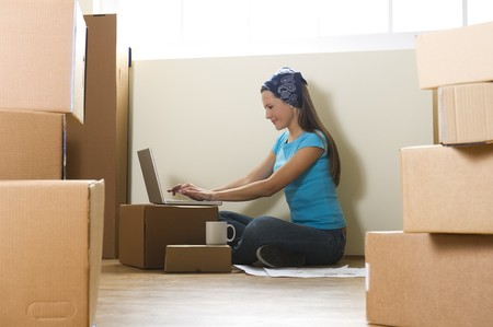 moving images: Woman with laptop in new home Stock Photo