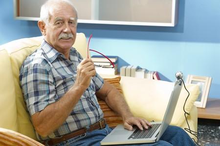 third age: Smiling senior man working at home Stock Photo