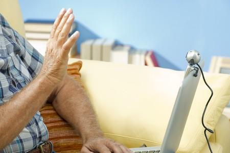 third age: Senior man speaking through webcam
