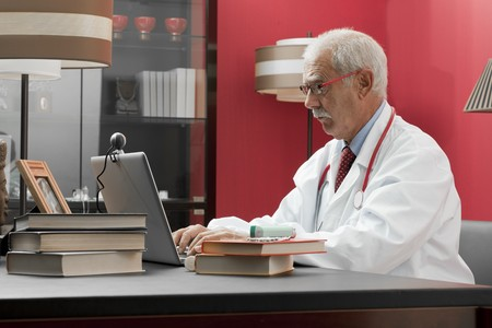 third age: Senrio doctor working in his studio Stock Photo
