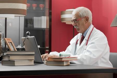third age: Senrio doctor working in his studio Stock Photo