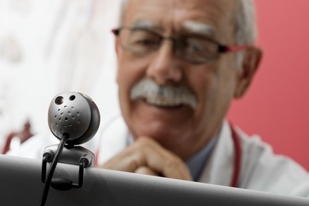 third age: Senior doctor speaking with patient through webcam Stock Photo