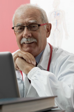 webcam: Senior doctor speaking with patient through webcam Stock Photo