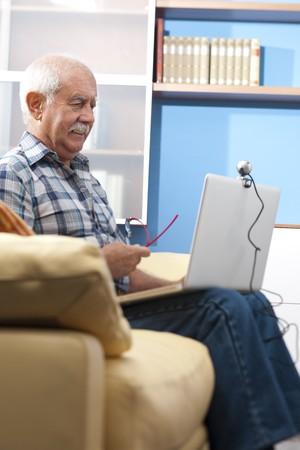 third age: Senior manGrandfther speaking through webcam