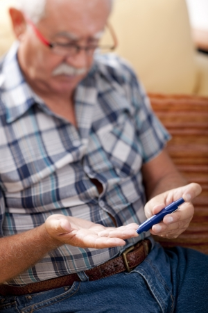 diabetes: Hombre Senior haciendo pruebas de az�car en la sangre en el hogar