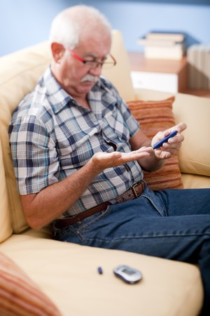Senior man doing blood sugar test at home photo