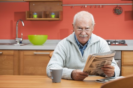 Senior man having coffee and reading newspaper in his kitchen photo