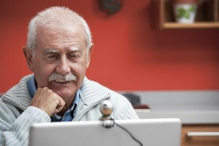 third age: Senior man speaking through webcam in his kitchen Stock Photo