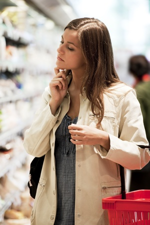 Pensive young woman at supermarket photo