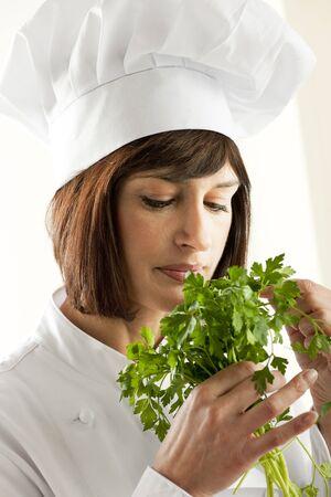Female Chef Smelling Parsley, white background photo