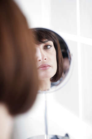 mirror face: Woman Looking At Herself In The Mirror
