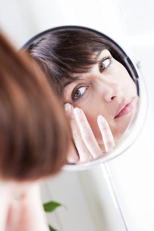 鏡で自分の姿を探している女性