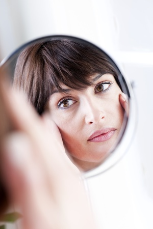 aging woman: Woman Looking At Herself In The Mirror
