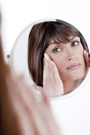 one mid adult woman only: Woman Looking At Herself In The Mirror
