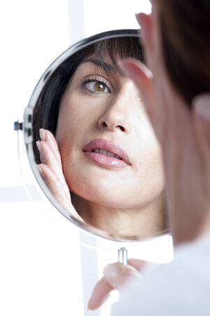 spiegels: Vrouw kijken naar zichzelf In de spiegel Stockfoto