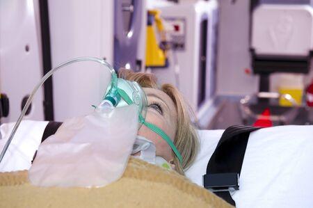 paciente en camilla: Herida mujer con máscara de oxígeno, interior de ambulancia