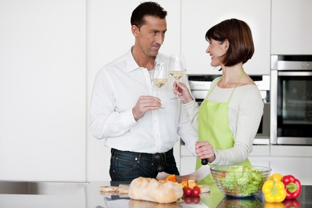 Happy Couple Toasting With Glass Of Wine while preparing dinner photo