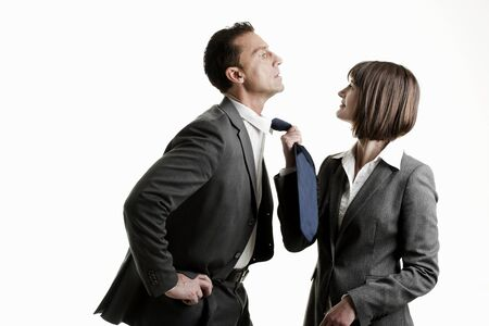 Businesswoman pulling her colleague from his tie photo