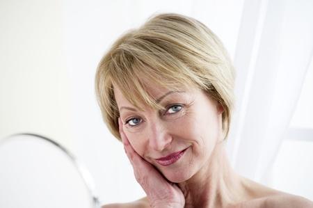 Beautiful mature woman making up (face)