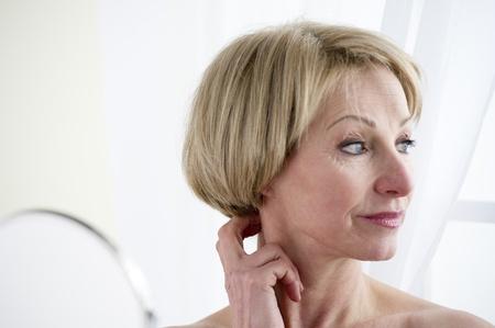 hand mirror: Beautiful mature woman making up Stock Photo